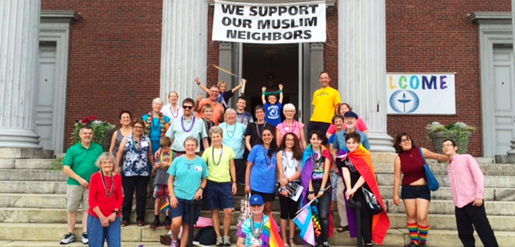 Members of First Unitarian Church on the steps celebrating Pride, with a rainbow Welcome banner in the background