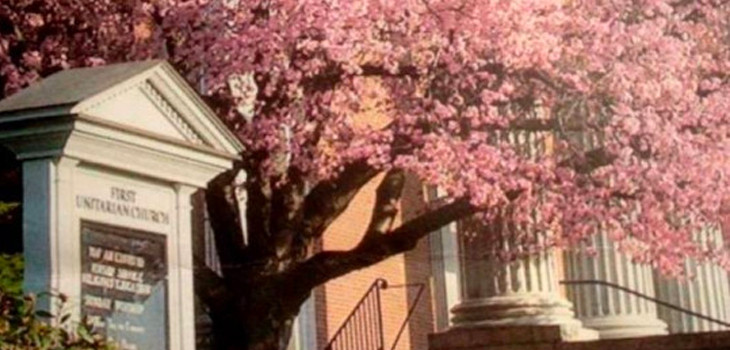 Wayside pulpit in front of First Unitarian Church with cherry tree in bloom