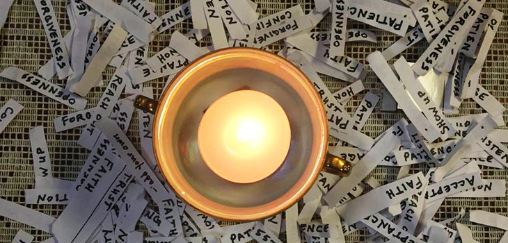 Flaming chalice surrounded by slips of paper with virtues written on them