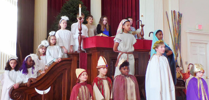 Children standing in and around the pulpit at First Unitarian Church, dressed in costume for the Christmas pageant