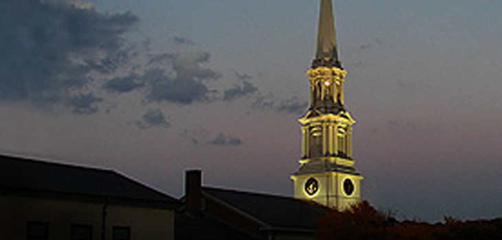 The lit steeple in the early evening